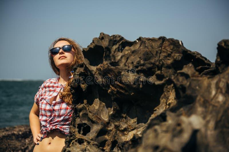 太阳镜的美女与放松在海岩石的性感的腹部 免版税库存照片