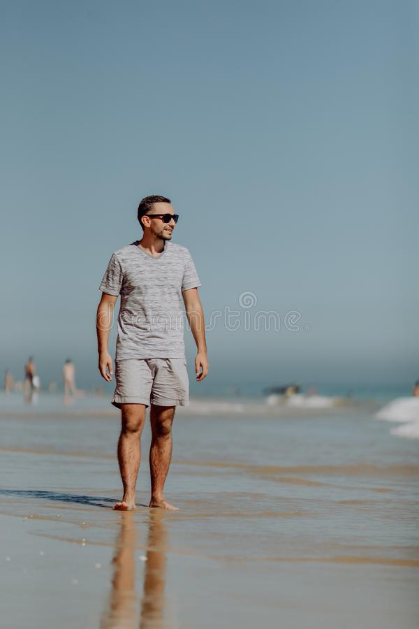 太阳镜的英俊的微笑的人走和享受在海滩的天 库存图片