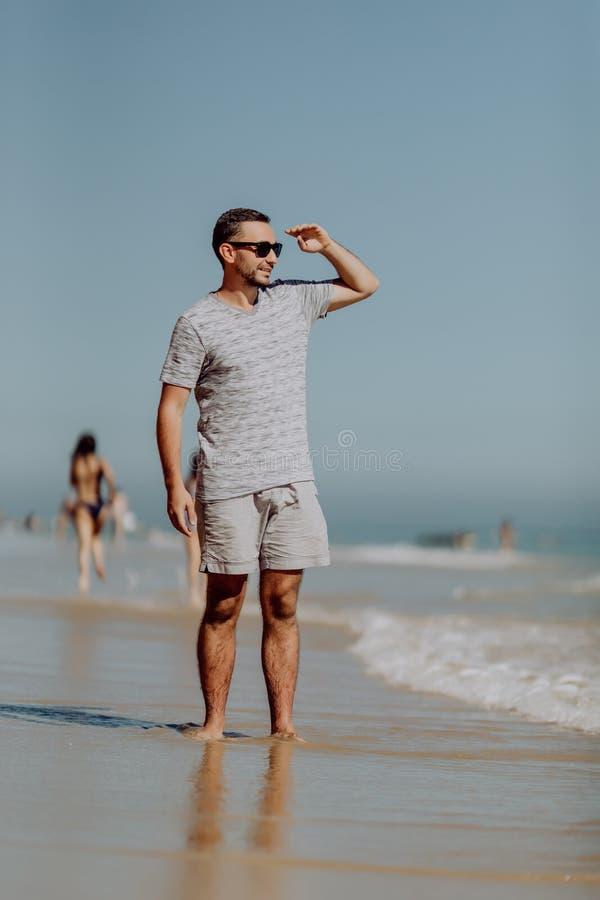 太阳镜的英俊的微笑的人走和享受在海滩的天 免版税库存照片