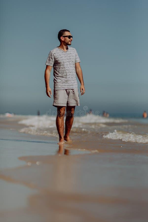 太阳镜的英俊的微笑的人走和享受在海滩的天 图库摄影