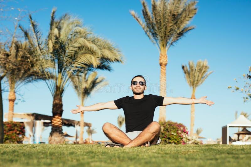 太阳镜的英俊的有胡子的人坐绿草和上升棕榈晒黑在棕榈和蓝天背景 免版税库存照片
