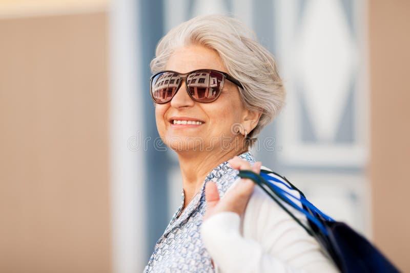 太阳镜的资深妇女有购物袋的 图库摄影