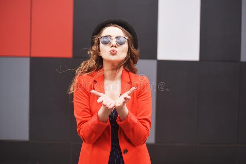 太阳镜的逗人喜爱的可爱的少妇、红色夹克和时尚帽子、身分和送亲吻在红色和黑背景 图库摄影