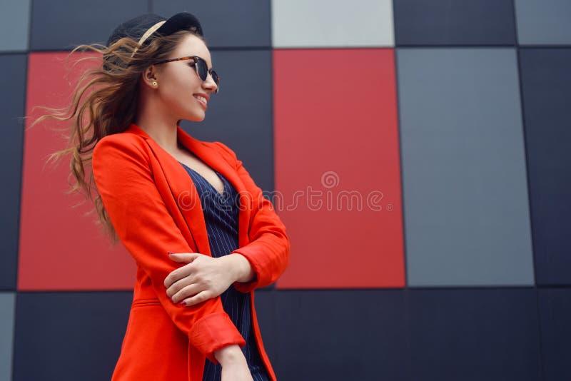太阳镜的逗人喜爱的可爱的少妇,红色夹克,时尚帽子,站立在室外抽象的背景 时装模特儿纵向 库存照片