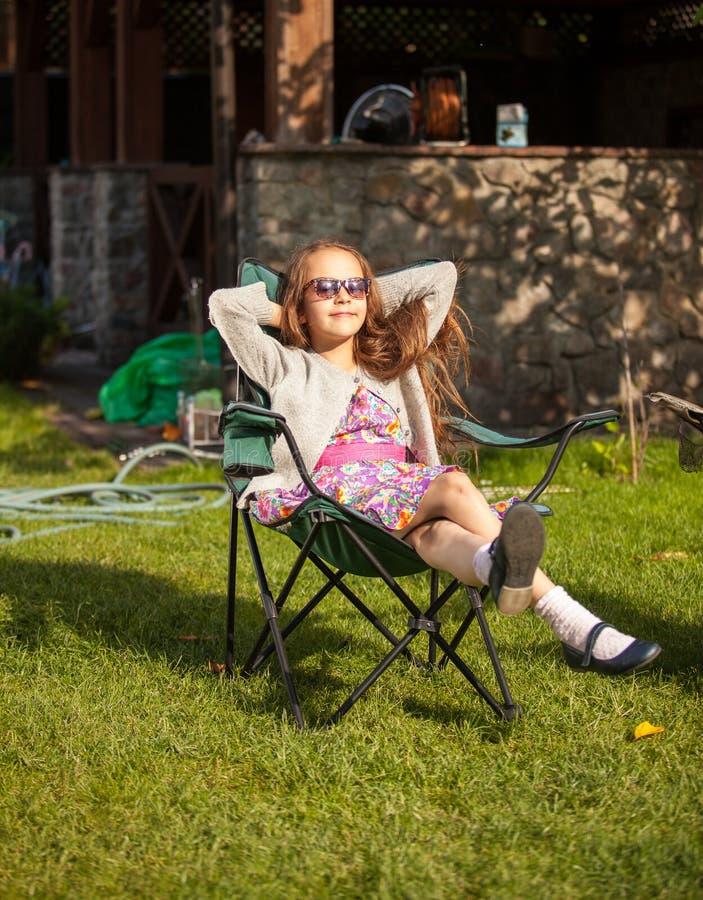 太阳镜的逗人喜爱的女孩晒日光浴在后院的 库存照片