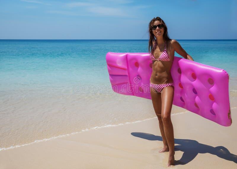 太阳镜的年轻亭亭玉立的深色的妇女在热带bea晒日光浴 免版税库存图片