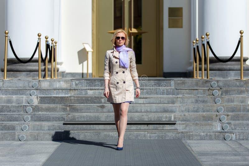 太阳镜走的典雅的白肤金发的女商人 免版税库存照片