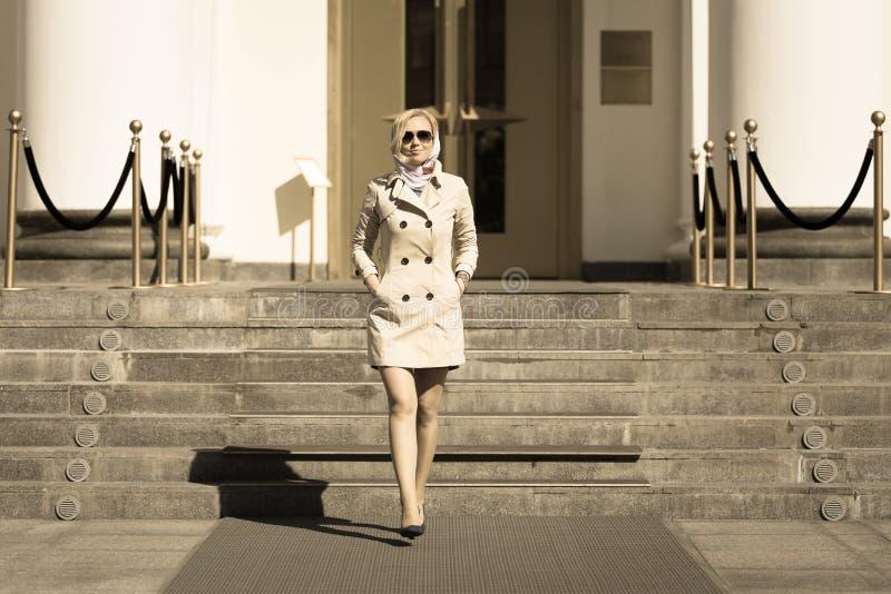 太阳镜走的时兴的白肤金发的企业夫人 免版税图库摄影