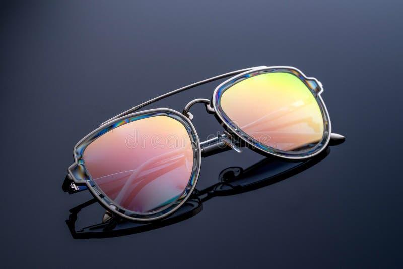 太阳镜,变色蜥蜴颜色,淡光在阳光下 黑暗的梯度背景 免版税图库摄影