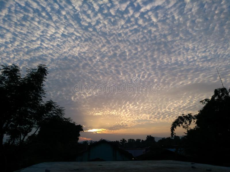 太阳集合,金黄天空的云彩 免版税库存图片