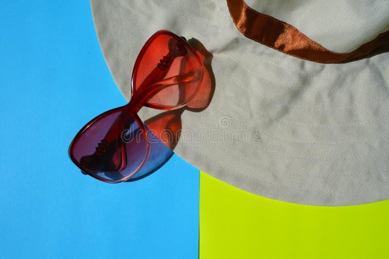 太阳风镜,在蓝色和黄色背景的帽子 免版税库存照片