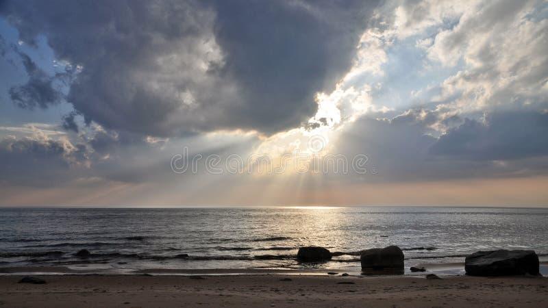 太阳` s通过在海上的云彩发出光线 库存照片