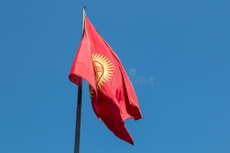 太飞行在丙氨酸正方形的吉尔吉斯斯坦的红色和黄旗在比什凯克,首都 库存照片