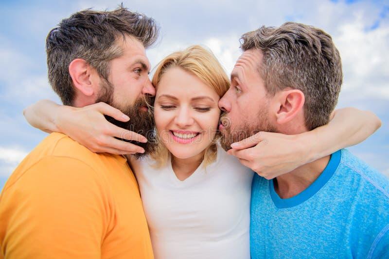 夫人享受浪漫联系两位钦佩者 她喜欢男性关注 三角爱 人亲吻同样女孩面颊 女孩 库存照片