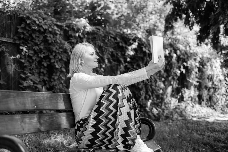 夫人俏丽的书痴繁忙的读的书户外好日子 文艺评论家 妇女被集中的看书在庭院里 库存图片