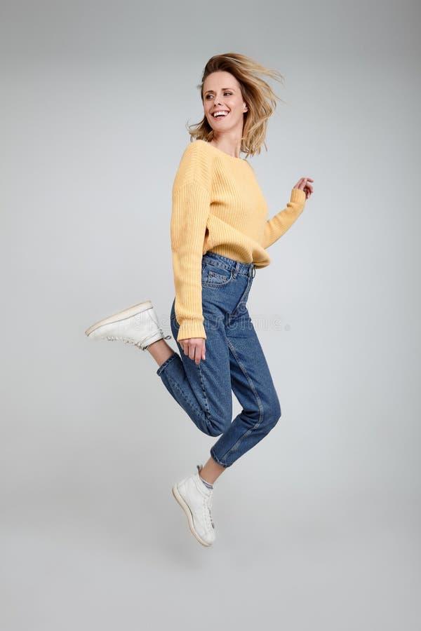夫人充分的腿身体尺寸画象用在旁边她的金发手她跳在明亮的白色隔绝的偶然成套装备的穿戴 免版税库存图片