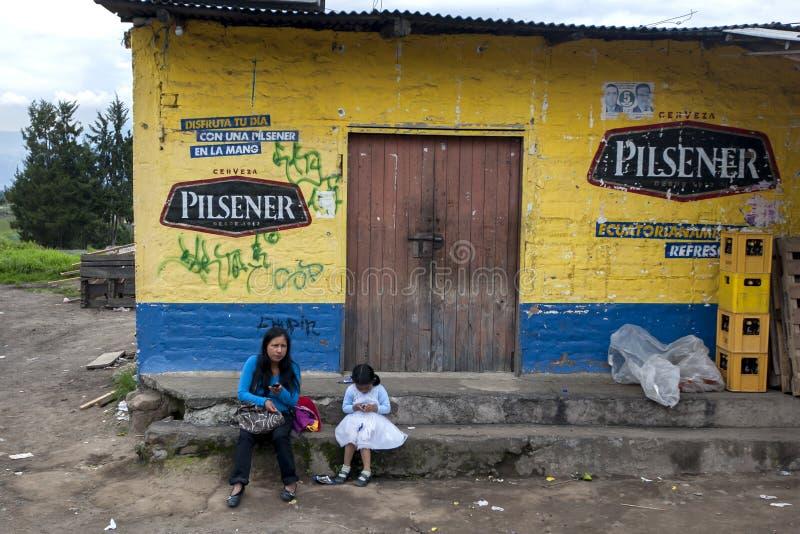 夫人和女孩坐一家五颜六色的商店外在Quinche的郊区在厄瓜多尔 库存照片