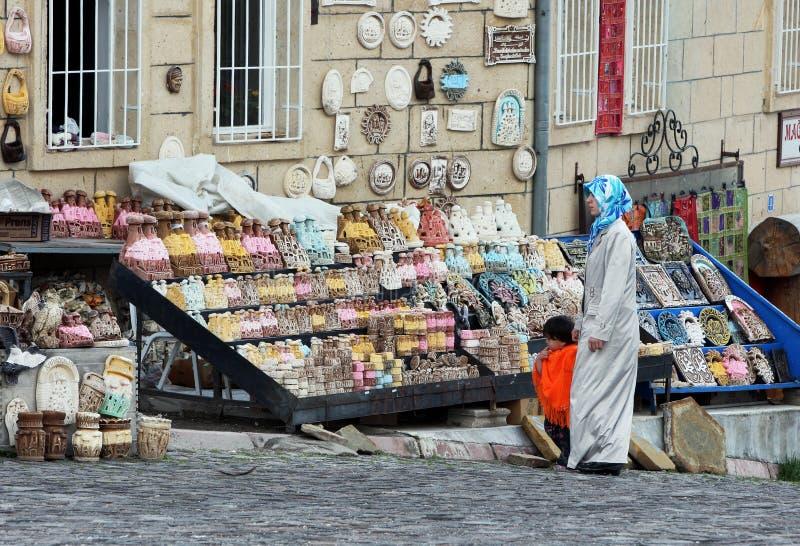 夫人和孩子看纪念品显示在街道上的待售Uchisar在土耳其 库存图片