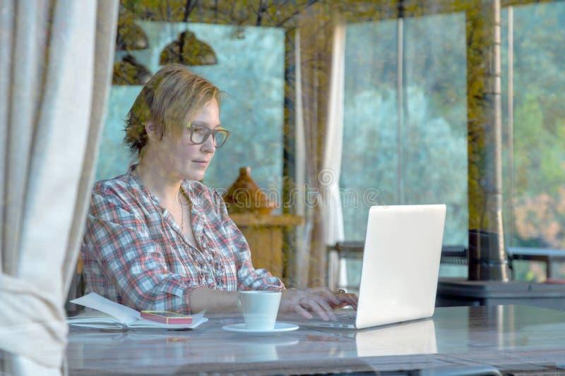 夫人在便携式计算机上的浏览互联网在咖啡馆 免版税库存图片