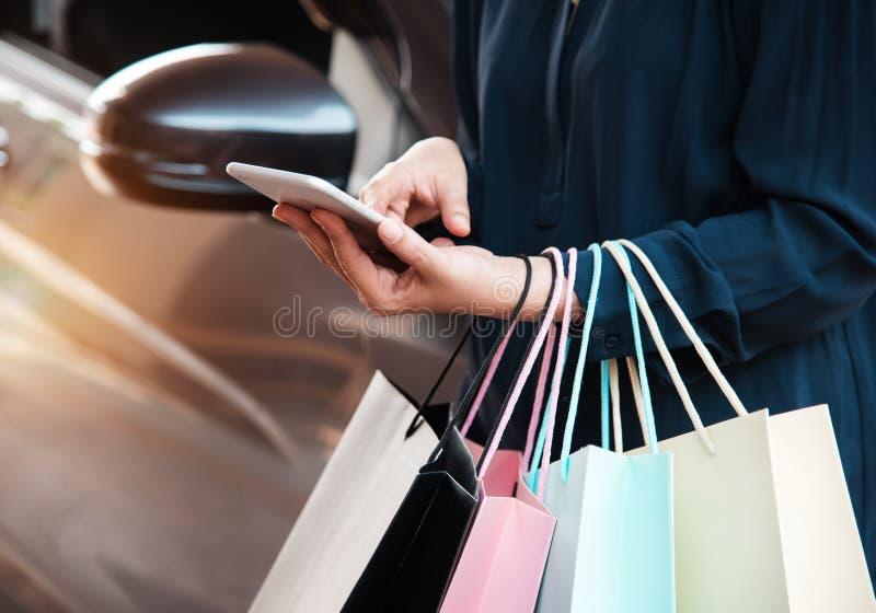 夫人在网上购物的手机紧迫的特写镜头,并且她拿着在左手边的五颜六色的购物袋 库存照片
