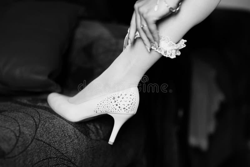 夫人在腿上把鞋带袜带放 库存图片