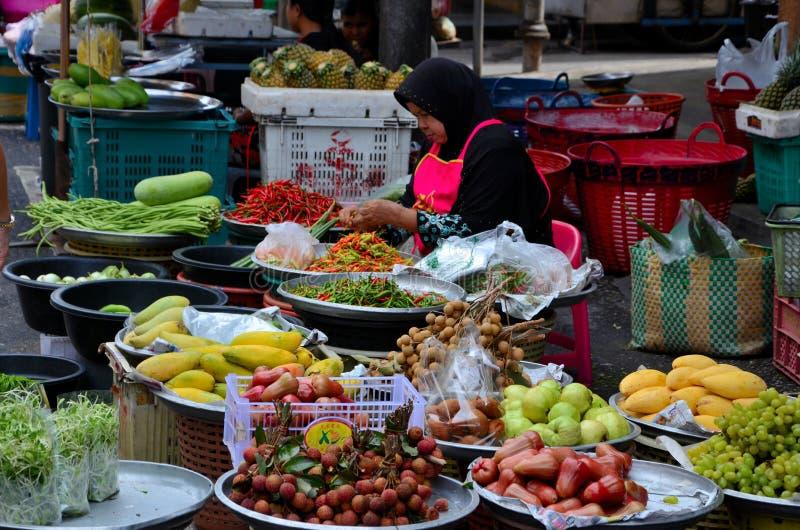 夫人在街市义卖市场Hatyai泰国卖新鲜水果&菜 免版税库存图片