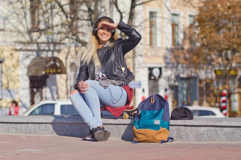 夫人女孩愉快的微笑,坐滑板 免版税库存图片