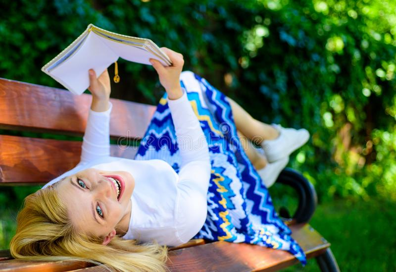 夫人愉快的面孔喜欢读 自我改善的时刻 女孩放置放松与书,绿色自然的长凳公园 免版税库存图片