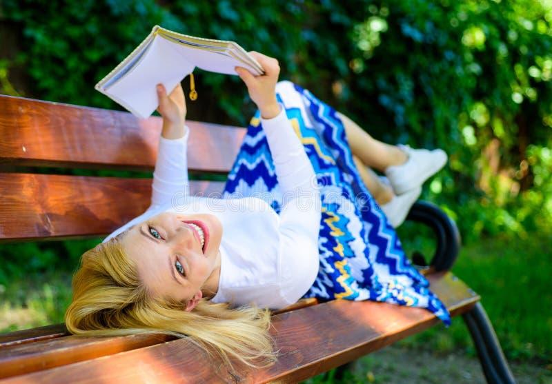 夫人愉快的面孔喜欢读 自我改善的时刻 女孩放置放松与书,绿色自然的长凳公园 库存照片