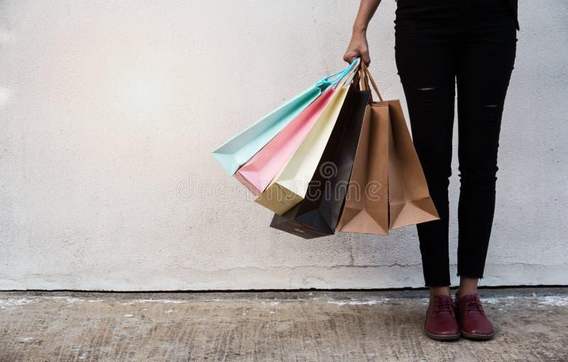 夫人拿着在她的右手的五颜六色的购物袋,她在水泥墙壁前面站立,在购物从大销售以后 免版税图库摄影