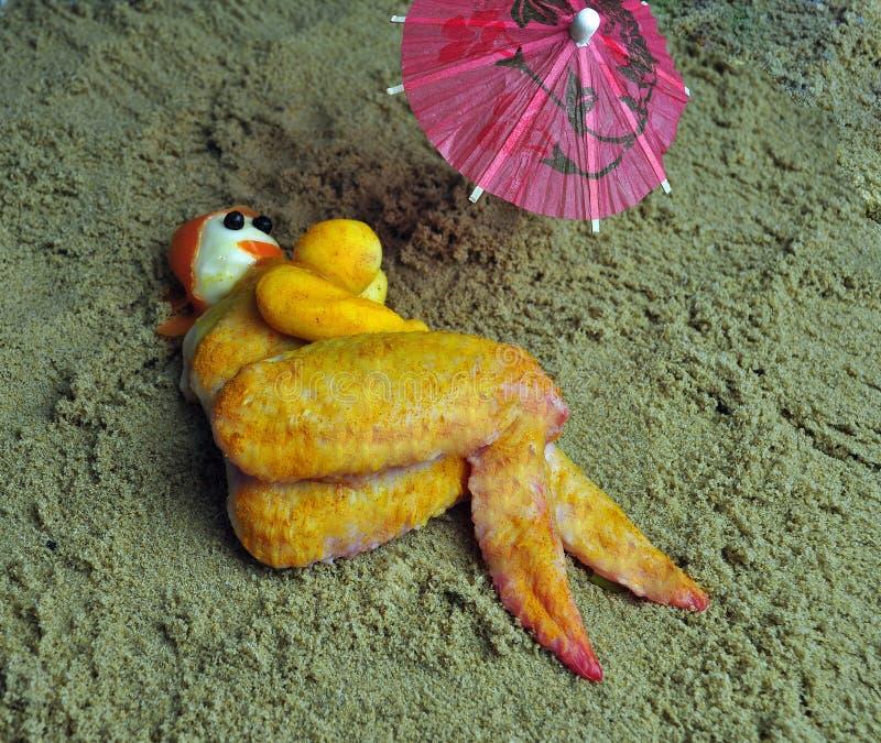 夫人由鸡制成在海滩食物艺术 免版税库存图片