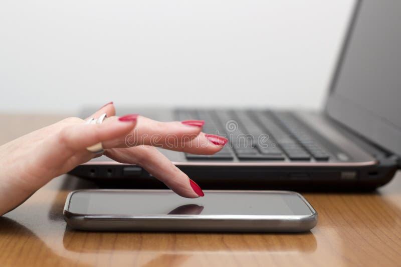 夫人的手指接触巧妙的电话 免版税库存图片