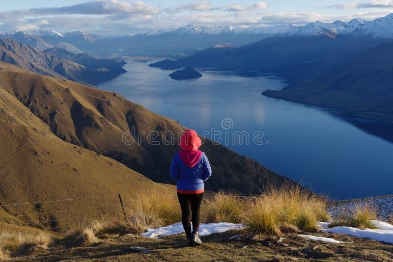 夫人远足者站立在山顶部的-以Wanaka湖为目的地峡峰顶 图库摄影