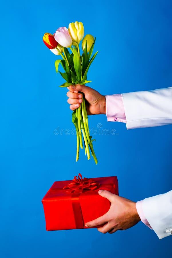 夫妇、关系和人概念-拿着花和礼物的人 意想不到的片刻在定期日常生活中 免版税库存照片