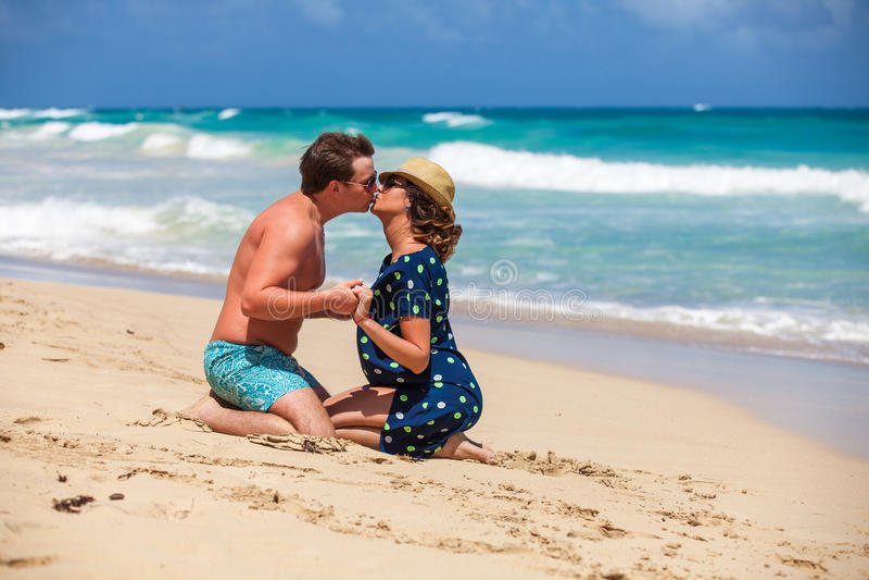 年轻夫妇一起坐沙子由海洋 免版税库存图片