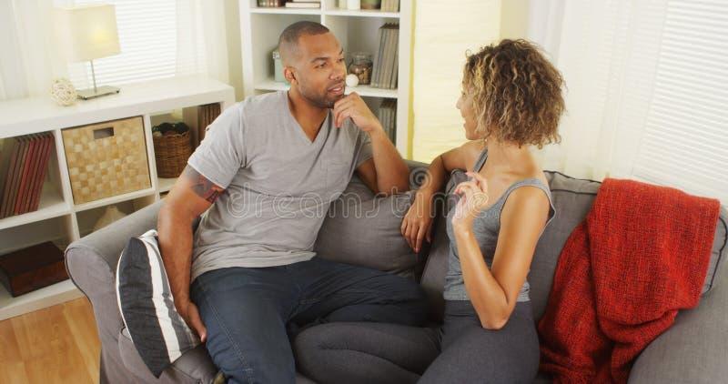 黑夫妇一起谈话在长沙发 免版税库存照片