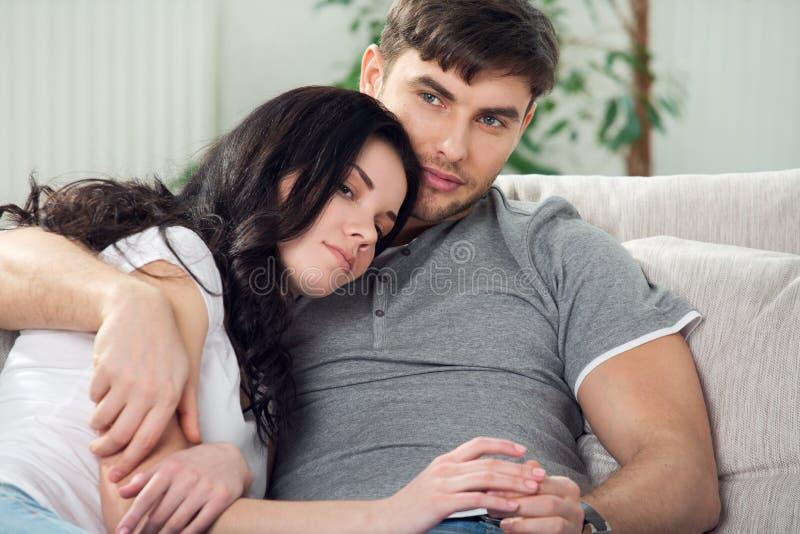 年轻夫妇下来坐长沙发 免版税图库摄影