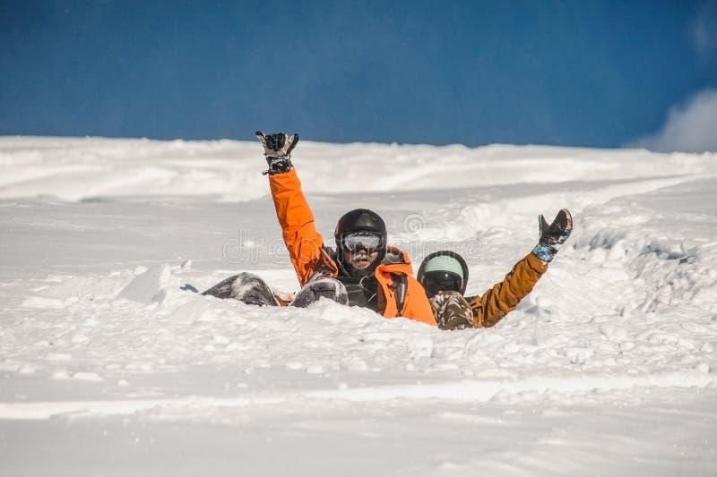 夫妇下落在摇他们的手的雪挡雪板倾斜 库存照片