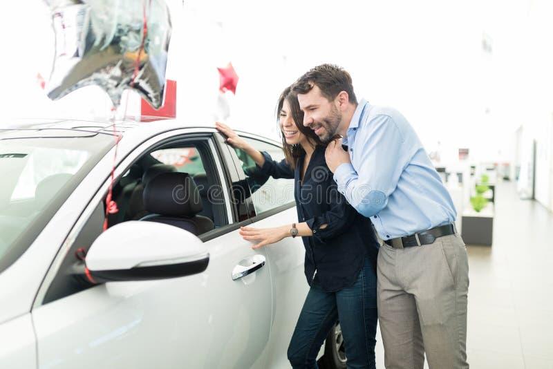 夫妇不可能停止敬佩他们新的汽车 免版税库存图片