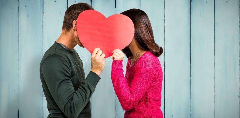 夫妇与心脏形状的覆盖物面孔的综合图象 图库摄影