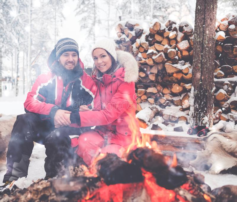 夫妇临近在冬天风景的篝火 库存图片