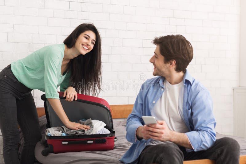 夫妇为旅行做准备,妇女包装手提箱 免版税库存图片