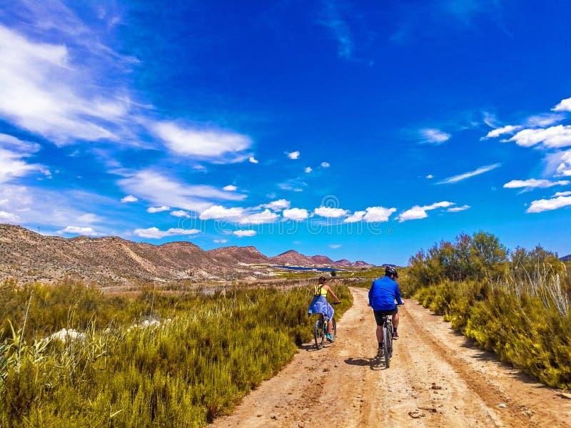 夫妇乘坐的自行车看法在一条土路的在美丽的parkland 免版税库存照片