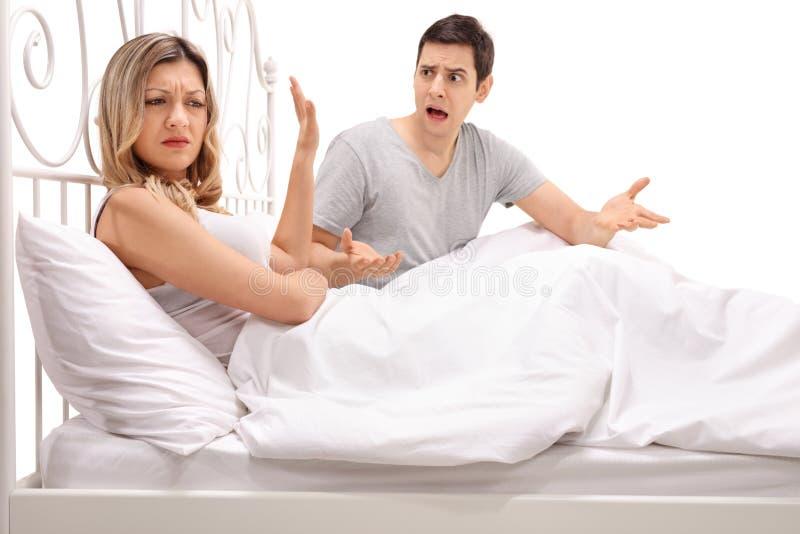 年轻夫妇争论在床上 免版税库存图片