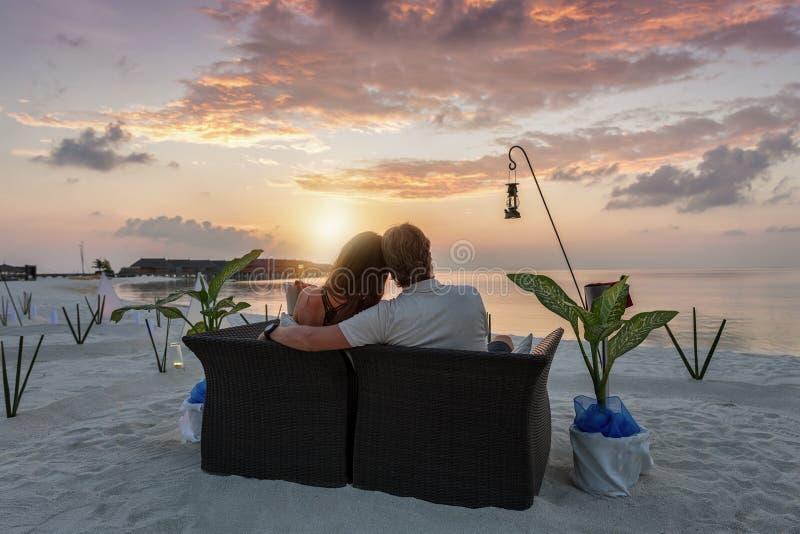 夫妇享受在一个热带海滩的日落事件 免版税库存照片