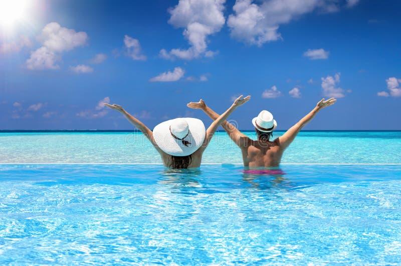 夫妇享受看法到游泳场的海 免版税图库摄影