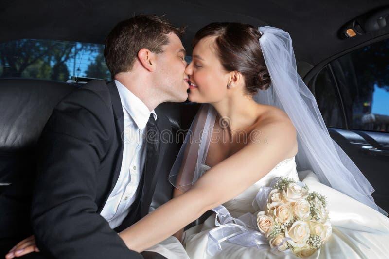 夫妇亲吻大型高级轿车婚礼 免版税库存照片