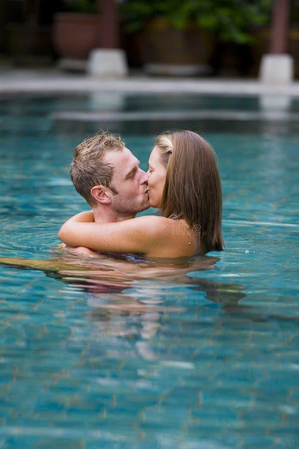 夫妇亲吻的池游泳 库存图片
