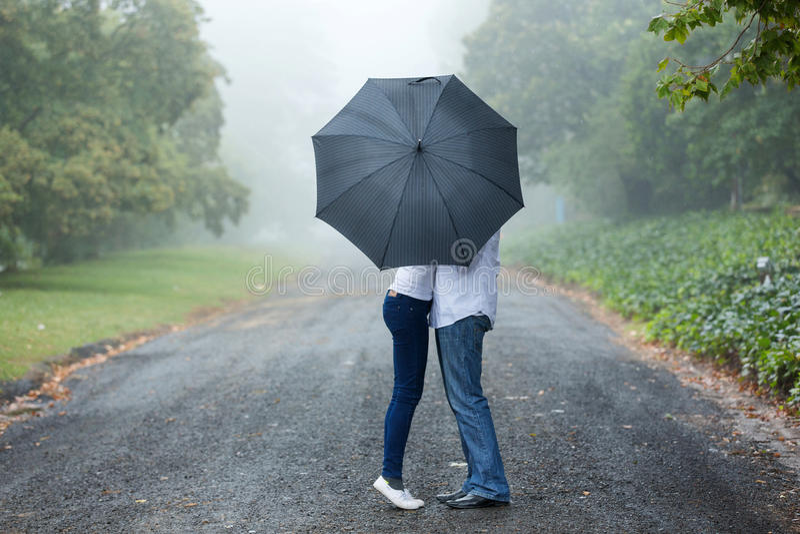 夫妇亲吻的伞 库存图片