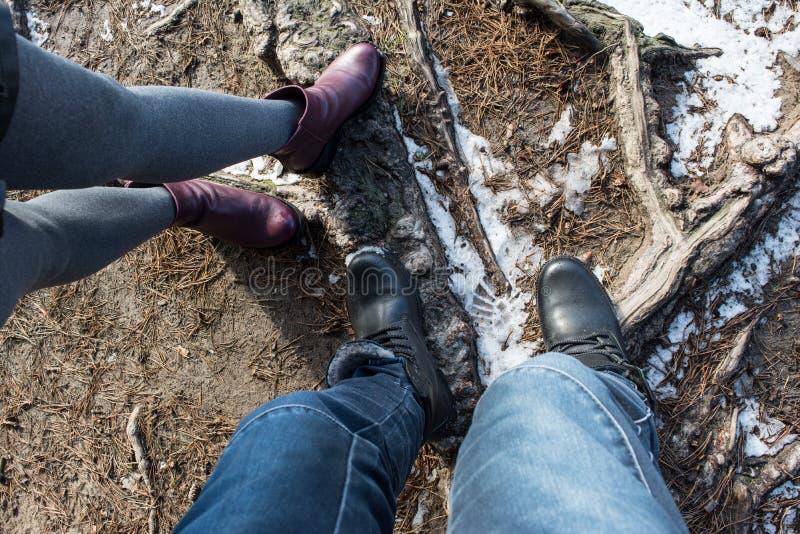 夫妇人和妇女佩带的鞋子和身分的腿在地面 免版税库存图片